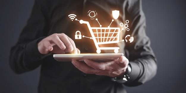 ショッピングカートでタブレットを使用するビジネスマン。 eコマース。オンラインショッピング