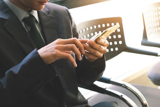 Бизнесмен, использующий смартфон. старинный тон, эффект ретро-фильтра, мягкий фокус, низкий свет. (селективный фокус)