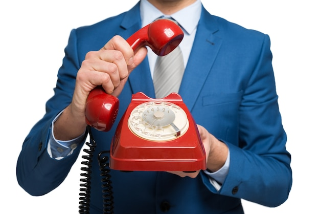 Businessman using a vintage phone, isolated on white