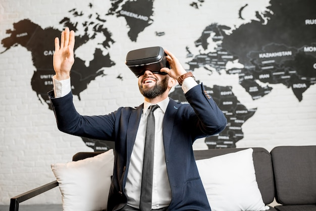 背景に世界地図と屋内に座ってバーチャルリアリティメガネを使用してビジネスマン