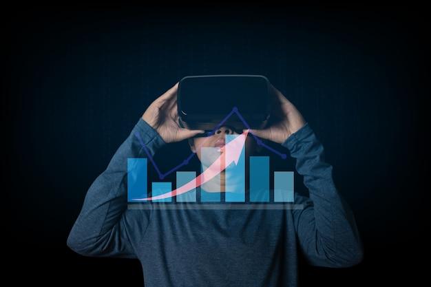 バーチャルリアリティヘッドセットを使用しているビジネスマン。株式市場投資ファンドとデジタル資産と外国為替取引グラフの財務データを分析します。テクノロジーオンラインコンセプト。