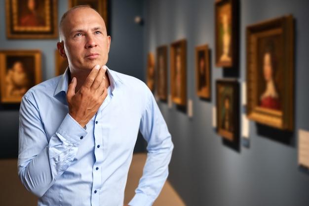 アートギャラリーで写真を探しているビジネスマンの訪問者