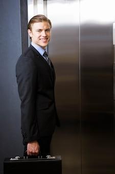사무실에서 엘리베이터를 기다리는 사업가
