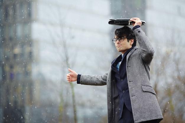 雪の中でタクシーを待っている実業家