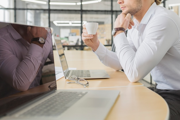 Businessman waiting in front of laptop