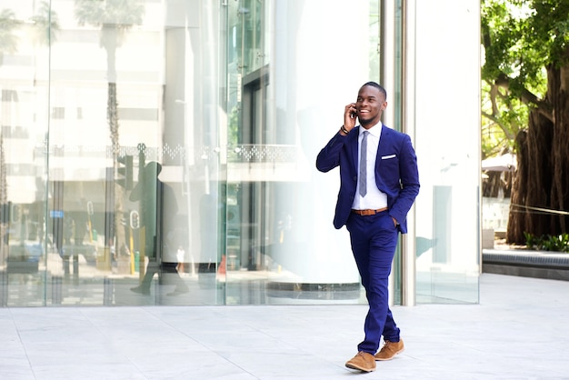 Businessman walking in the city using mobile phone