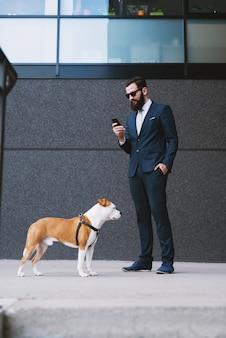 Собака бизнесмена прогулки на улице. лучшие друзья гуляют. собака битника красивого бизнесмена гуляя.