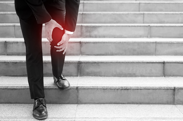 A businessman walking down the stairs, his knee ached.