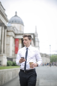 Businessman walking in front of the national gallery in london