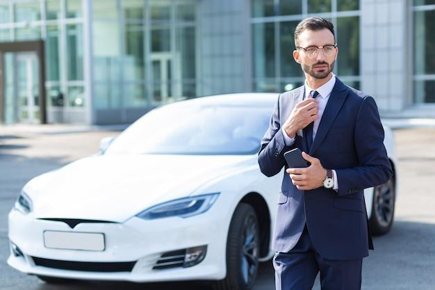 Бизнесмен гуляет. красивый бородатый бизнесмен держит телефон и идет в офис