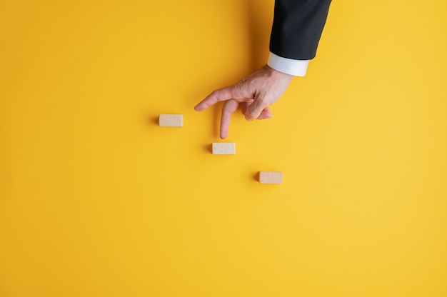 Businessman walking his fingers up the metaphorical steps. over yellow wall with copy space.