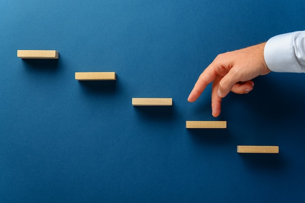 Businessman walking his fingers up a stairway made of wooden pegs in a conceptual image. over navy blue background.