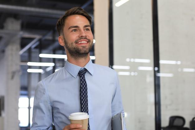 테이크아웃 커피와 함께 사무실 복도를 걷고 있는 사업가.