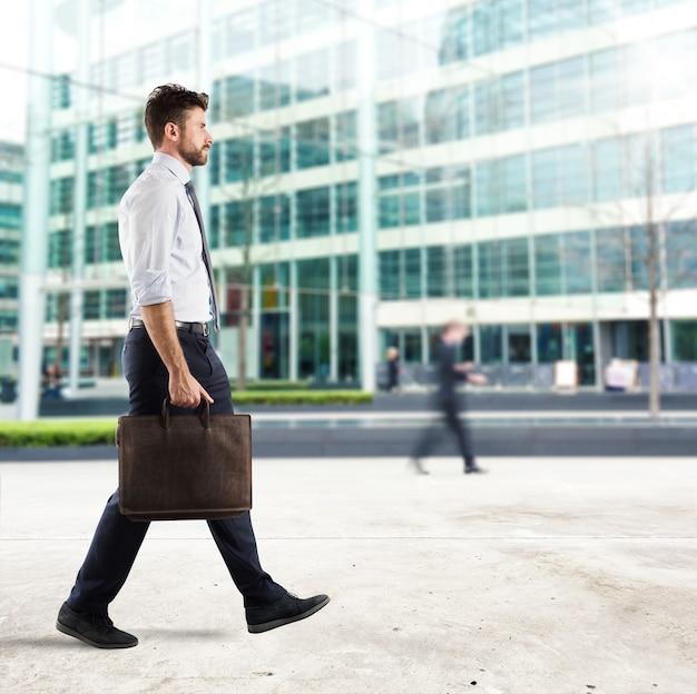 Бизнесмен, идущий по улице с фоном небоскреба
