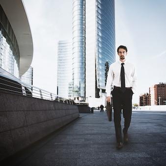 Бизнесмен, идущий по улице с небоскребом