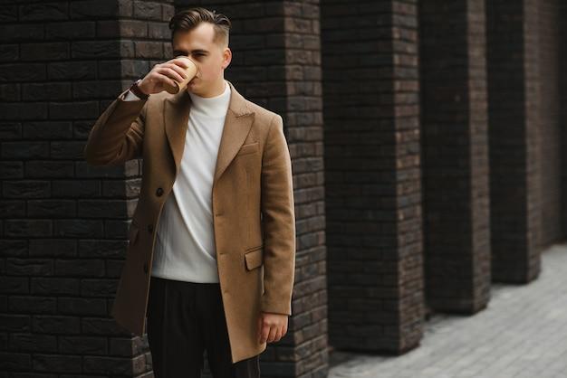 コーヒーを飲みながら公共交通機関の建物の外を歩いて目をそらすビジネスマン