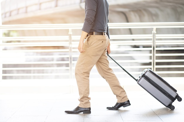 ラッシュアワーに荷物を持って公共交通機関の建物の外を歩くビジネスマン。現代の空港ターミナルでスーツケースを引っ張るビジネス旅行者。手荷物出張。