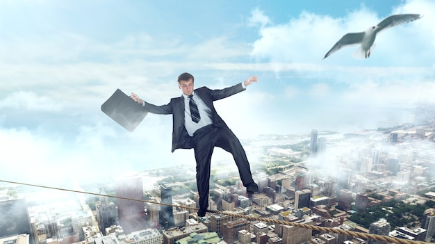 Businessman walking on a rope over the business center. bankruptcy risk, financial balance concept