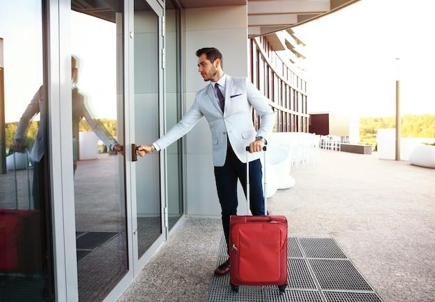 호텔 로비에 산책하는 사업가. 가방으로 젊은 경영자의 전체 길이 초상화.