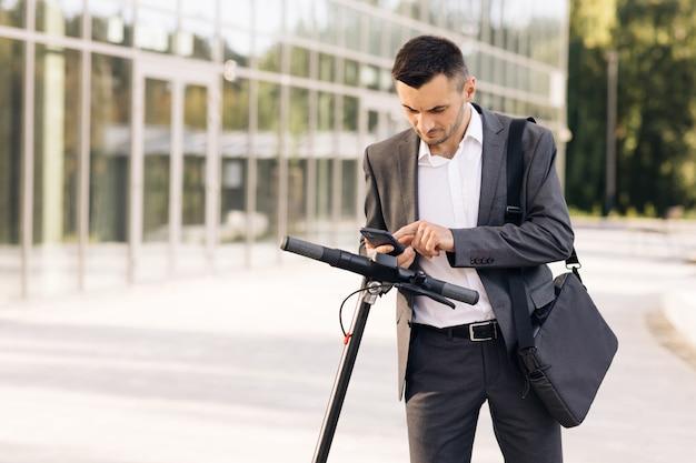Бизнесмен, идущий к своему туристическому эскутеру, берет электрический скутер в эко-парковке