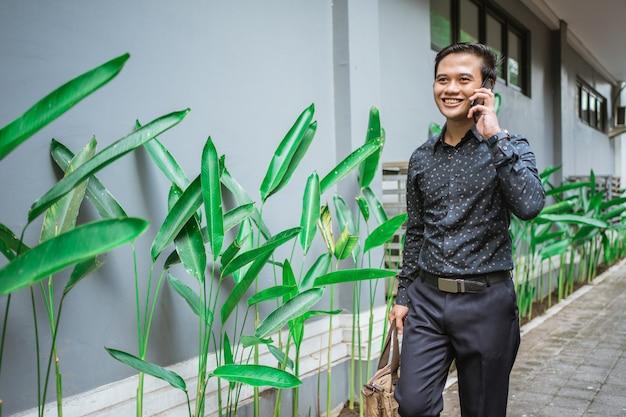Бизнесмен, идущий по тротуару, улыбаясь, идет в офис с телефоном