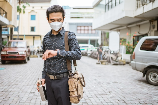 彼の腕時計を見て微笑んで歩道を歩くビジネスマン