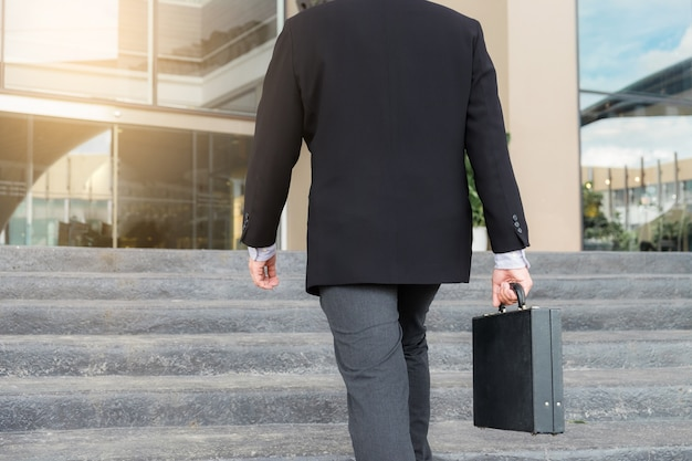 Businessman walking up the stairs and holding a briefcase in hand working with confidence