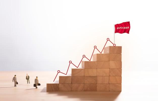 Бизнесмен идет вверх по лестнице на вершину горы деревянных блоков