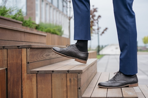 Businessman walking upstairs focus on leather shoe startup successful business career concept