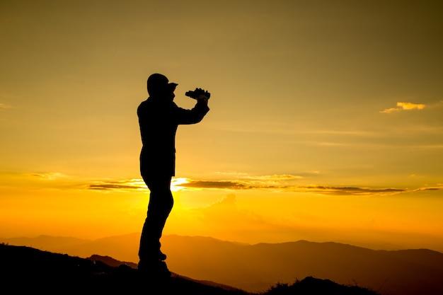 Бизнесмен смотрит в бинокль за свое видение на высокой горе