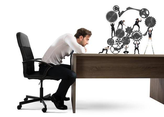 ビジネスマンは、ビジネスマンのチームワークがギアのシステムに一緒に働くのを見ます