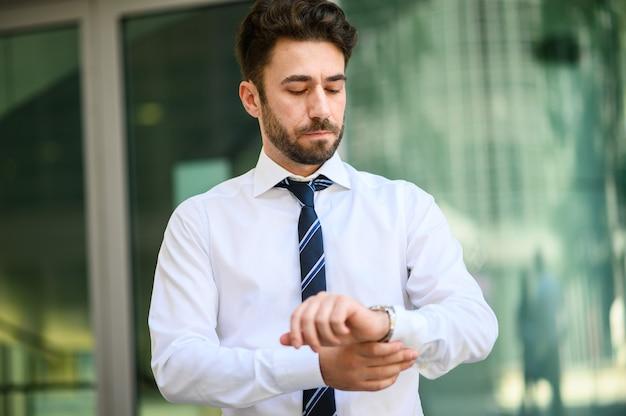 現代の都市で時間を見てビジネスビジネスマン