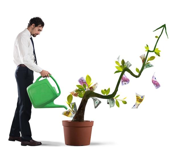 Бизнесмен поливает денежные монеты, как если бы они были растения
