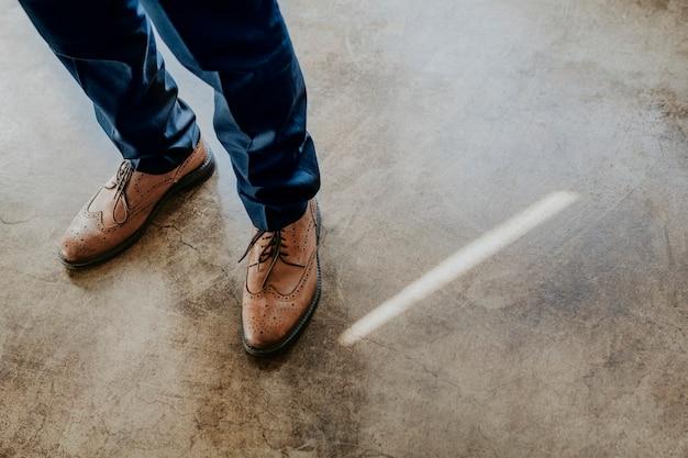 茶色の革の靴を履いているビジネスマン