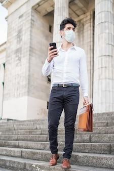 얼굴 마스크를 착용하고 야외에서 걷는 동안 자신의 휴대 전화를 사용하는 사업가