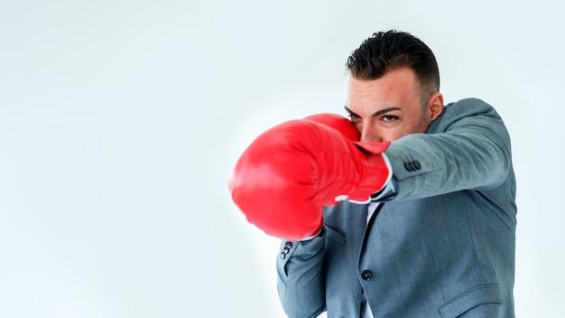 Бизнесмен носить боксерские перчатки и пробивать или охранять на белой стене.