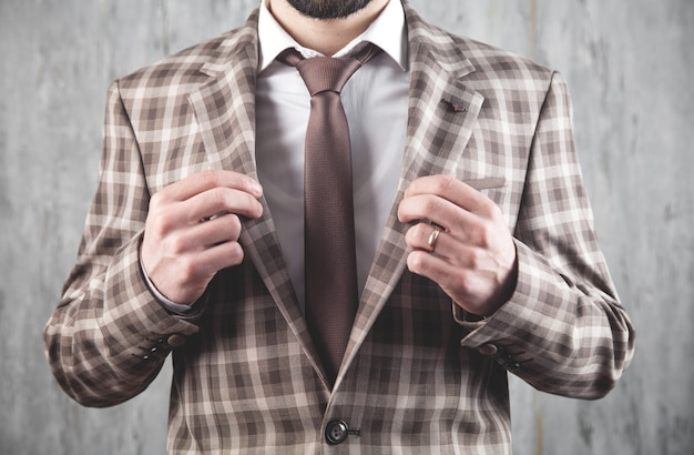 Бизнесмен носить коричневый галстук и пиджак, стоя в офисе.