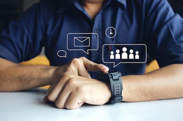 手首に通知読み取りメッセージとアクティビティトラッカーを開くために画面に触れる手でデジタルスマートウォッチを身に着けているビジネスマン
