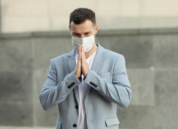 ウイルスの拡散を防ぐためにフェイスマスクを着用し、ナマステで挨拶するビジネスマン
