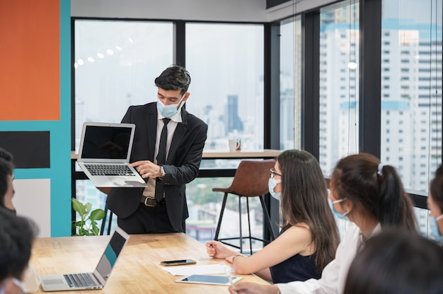 Businessman wearing face mask presentation of business plan on laptop in multiethnic business meeting at modern office during pandemic of coronavirus