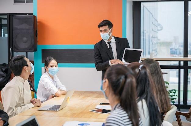 Бизнесмен в маске презентации бизнес-плана на ноутбуке на многонациональной деловой встрече в современном офисе