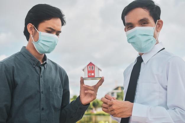 フェイスマスクを身に着けているビジネスマン、セールスマンは顧客に家を売ります