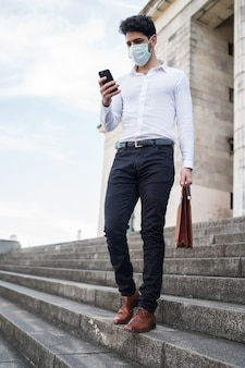 Businessman wearing a face mask and using his mobile phone while walking outdoors