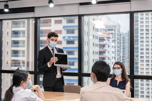 Бизнесмен в маске с презентацией бизнес-плана на ноутбуке корпоративная деловая встреча в современном офисе