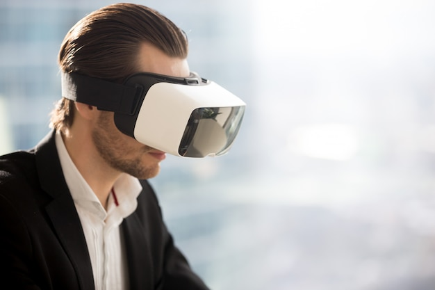 Businessman wearing futuristic virtual reality glasses.