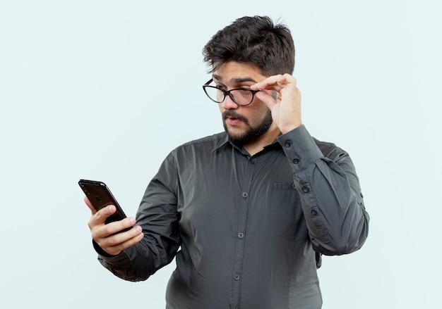 Uomo d'affari con gli occhiali tenendo e guardando il telefono isolato su bianco