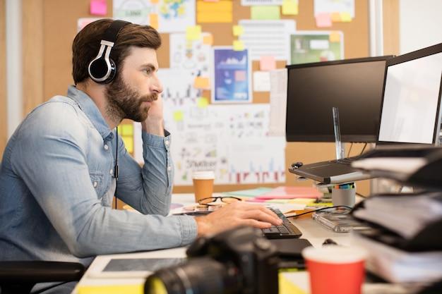 창조적 인 사무실에서 작업하는 동안 헤드폰을 착용하는 사업