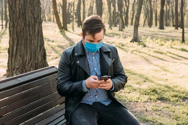 スマートフォン、ヘルスケアの概念を使用してマスクを身に着けているビジネスマン。コロナウイルス検疫。