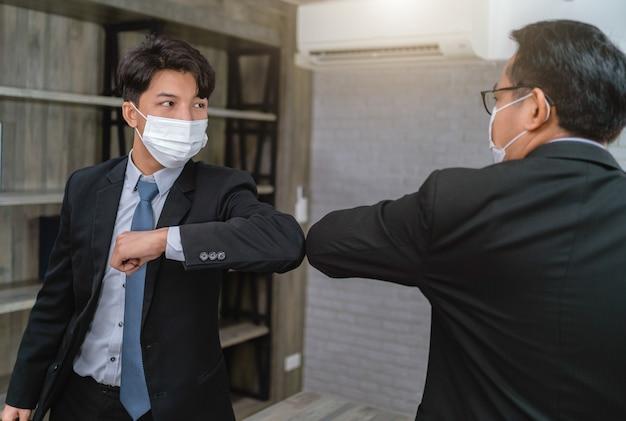 직장에서 부딪 치는 팔꿈치 인사말 보호 얼굴 마스크를 착용하는 사업가. 사무실에서 covid-19로부터 보호하십시오. 건강 관리 개념