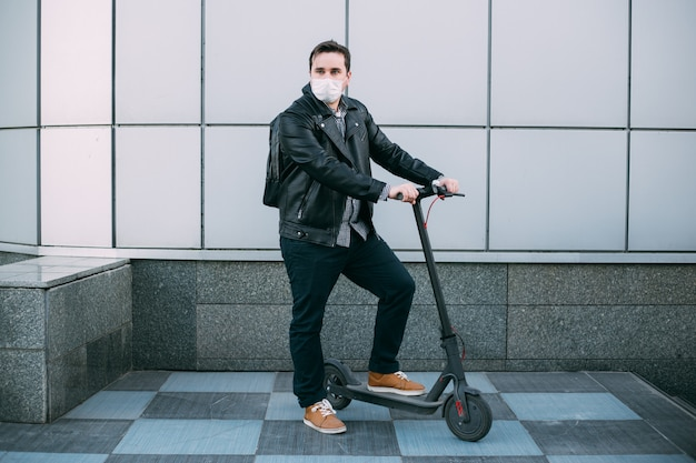 Businessman wearing protective mask using electric scooter
